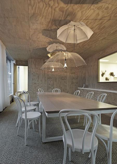 skėčiai šviestuvai prie lubų virš didelio stalo