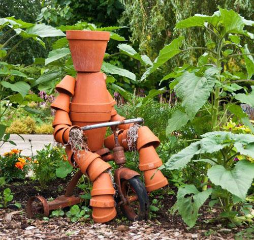 sodo dekoracija žmogeliukas iš vazonėlių ant dviračio